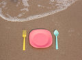 Still life plastic dishware utensil waiting clean food on the beach Royalty Free Stock Photos
