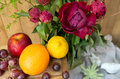 Still life of red peony flowers with fruit on wooden background Royalty Free Stock Photo