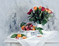 Still life with red pomegranate, orange tangerines and roses Royalty Free Stock Photo