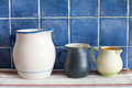 Still life with retro design ceramic jugs on napkin. Blue tiled wall background. Kitchen interior. Royalty Free Stock Photo