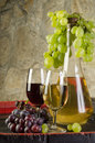 Still life with ripe grapes, wine glasses and wine bottles in old cellar Royalty Free Stock Photo
