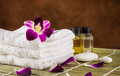 Still life spa setting and orchid flower with towels aroma oil on dark fabric background Royalty Free Stock Photos