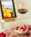 Still life with strawberries, coffee and a glass of red wine and a photo of a seaside resort Royalty Free Stock Photo