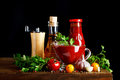 Still life with tomatoes, parsley, garlic, olive oil and tomato sauce on wooden boards. On a black background. Royalty Free Stock Photo