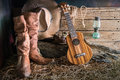 Still life with ukulele on cowboy hat and traditional leather bo Royalty Free Stock Photo