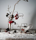 Still life. viburnum branches with berries and snow in a transparent vase, glass teapot on wooden table
