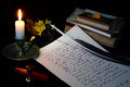Still life with vintage writing instruments a letter a pen a lighted candle in copper candlestick and a pile of old books on a Stock Images