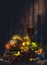 Still life with wine, grapes, bread and various sorts of cheese. Royalty Free Stock Photo