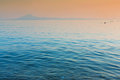 Still sea and distant island calm at sunset in thassos greece Royalty Free Stock Image