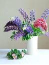 Stilleben en vit vas med purpurfärgad och rosa lupine och rosa färger fl Royaltyfria Foton