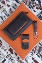 Stillife of handmade leather set for men including wallet keyring and manicure