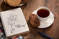 Stilllife with a cup of black tea on the wooden table beautiful reprented saucer cookies there is picture flower in notebook Stock Photos