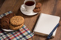 Stilllife with a notebook and cookies on the wooden table start your beautiful morning blank page in Royalty Free Stock Photo
