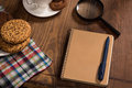 Stilllife with a notebook on the wooden table covered by loupe cookies pen etc you may start your morning different ideas Stock Images