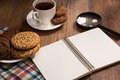 Stilllife with a notebook on the wooden table an opened covered by loupe cookies cup of black tea etc you re to start your new Stock Photo