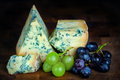 Stilton mature blue mouldy cheese dark background and grapes green black Royalty Free Stock Photography