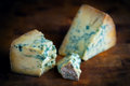 Stilton mature blue mouldy cheese dark background on wooden board Stock Photo
