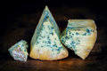 Stilton mature blue mouldy cheese dark background on wooden board Royalty Free Stock Images