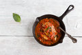 Stir-fried chicken breast in a sauce of tomatoes, garlic, basil and olive oil. Black cast-iron pan, light wooden table, top view Royalty Free Stock Photo