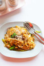 Stir fried chicken noodle thai style with and vegetable in thai countryside restaurant Stock Photo