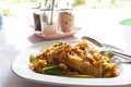 Stir fried chicken noodle thai style with and vegetable in thai countryside restaurant Stock Photos