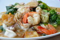 Stir-fried large noodle with seafood in gravy sauce on plate Royalty Free Stock Photo
