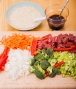 Stir fry ingredients vertical beef on cutting board with rice and soy sauce in background Royalty Free Stock Image