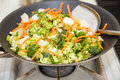 Stir fry vegetables in a hot wok with spatula Stock Photos