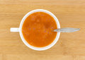 Stirred cup of fiber laxative in water with spoon a white filled and orange on a wood table top Stock Image