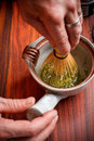 Stirring matcha tea with whisk Stock Photo