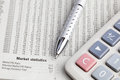 Stock data metal pen and calculator placed on newspaper Royalty Free Stock Photos