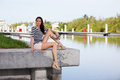 Stock image woman sitting on a ledge attractive young by the water Stock Photo