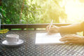 Stock photo :Coffee cup with closeup man writing a notebook on Royalty Free Stock Photo