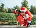 Stock photo of Santa Claus without beard playing with a German shepherd dog who is pulling him out of the gift bag. Christmas time Royalty Free Stock Photo