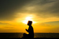 Stock photo woman doing yoga at sunset silhouette of a against the sky Royalty Free Stock Photography