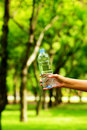 Stock photo woman hand holding water bottle against green back background Royalty Free Stock Images
