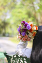 Stock photo young girl sitting on a bench in a large bouquet of flowers Stock Photography