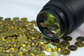Stock photography concept photo lens with money reflection on the glass and pile of coins in the foreground Stock Photography