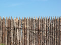 Stockade wooden fence on blue sky background Royalty Free Stock Photo
