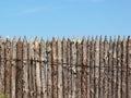 Stockade wooden fence on blue sky background Royalty Free Stock Photo