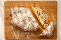 Stollen a loaf of cake on a board two slices and lit from a window Royalty Free Stock Image