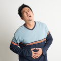 Stomach pain asian male with painful face expression on plain background Royalty Free Stock Images