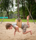 Stomach swinging a young boy on the swingset on his belly with his legs and arms flaying Royalty Free Stock Images