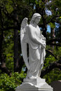 Stone angel gravestone in peaceful cemetery Stock Photo