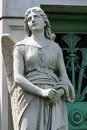 Stone angel guardian statue a of a young female guards the green weathered door to a mausoleum at graceland cemetery chicago Royalty Free Stock Photo