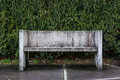 Stone Bench Grungy Against Green Bush Leaves Background Closeup Royalty Free Stock Photo