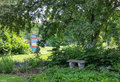 Stone bench under shady tree in yard with colorful bee hives peaceful area providing a place to rest Stock Photos