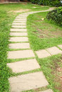 Stone block walk path in the park with green grass background Stock Photography