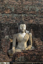 Stone Buddha with brick background Stock Photo