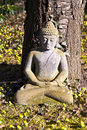 Stone buddha meditation in front of a cherry tree Royalty Free Stock Photos